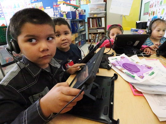 Cristopher Piedra, 5, left, works a lesson on an iPad