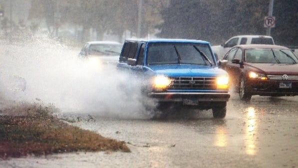 Motorists go through rain-filled roads on Kiwanis Avenue.