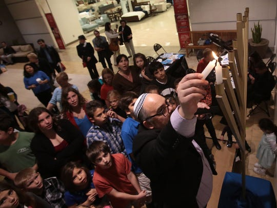 Rabbi Andrew Bentley of Temple Sinai lights the first