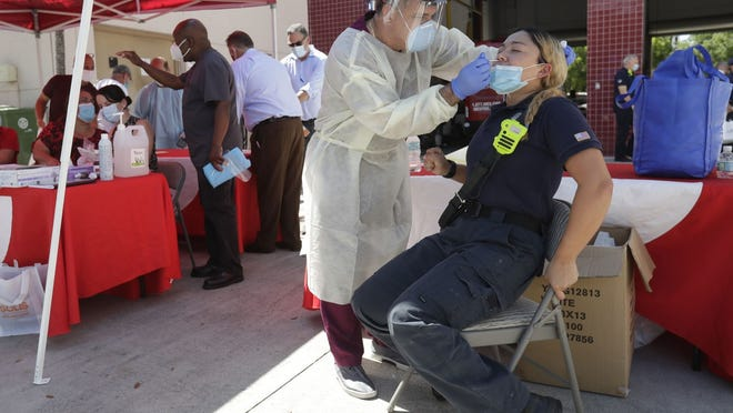 In this Aug. 6 file photo, Hialeah Fire Department Firefighter-Paramedic Laura Nemoga, right, winces as medical assistant Jesus Vera performs a COVID-19 test  in Hialeah, Fla.