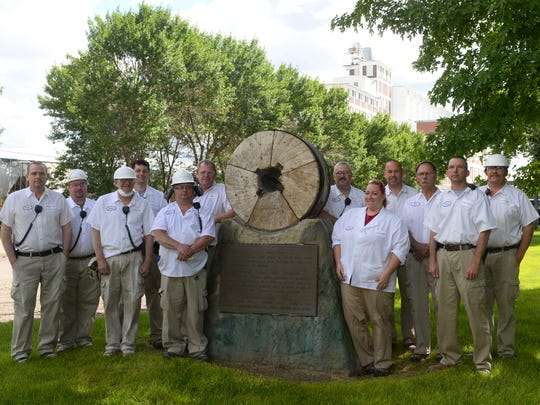 Grain Craft employees flank the millstone in front of the Montana Flour Mills building, which turns 100 this year.