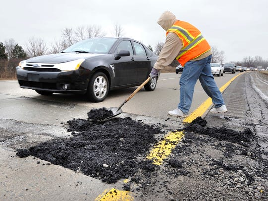 An Oakland Co. Road Commission worker fills a large pothole on I-59 westbound just east of Crooks Road.