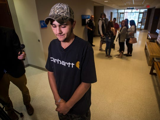 Caleb Moore, 16, of Burlington talks to the media about