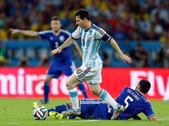 Argentina's Lionel Messi strolls past Bosnia's Sead Kolasinac during the group F World Cup soccer match between Argentina and Bosnia at the Maracana Stadium in Rio de Janeiro, Brazil, Sunday, June 15, 2014.  (AP Photo/Victor R. Caivano)