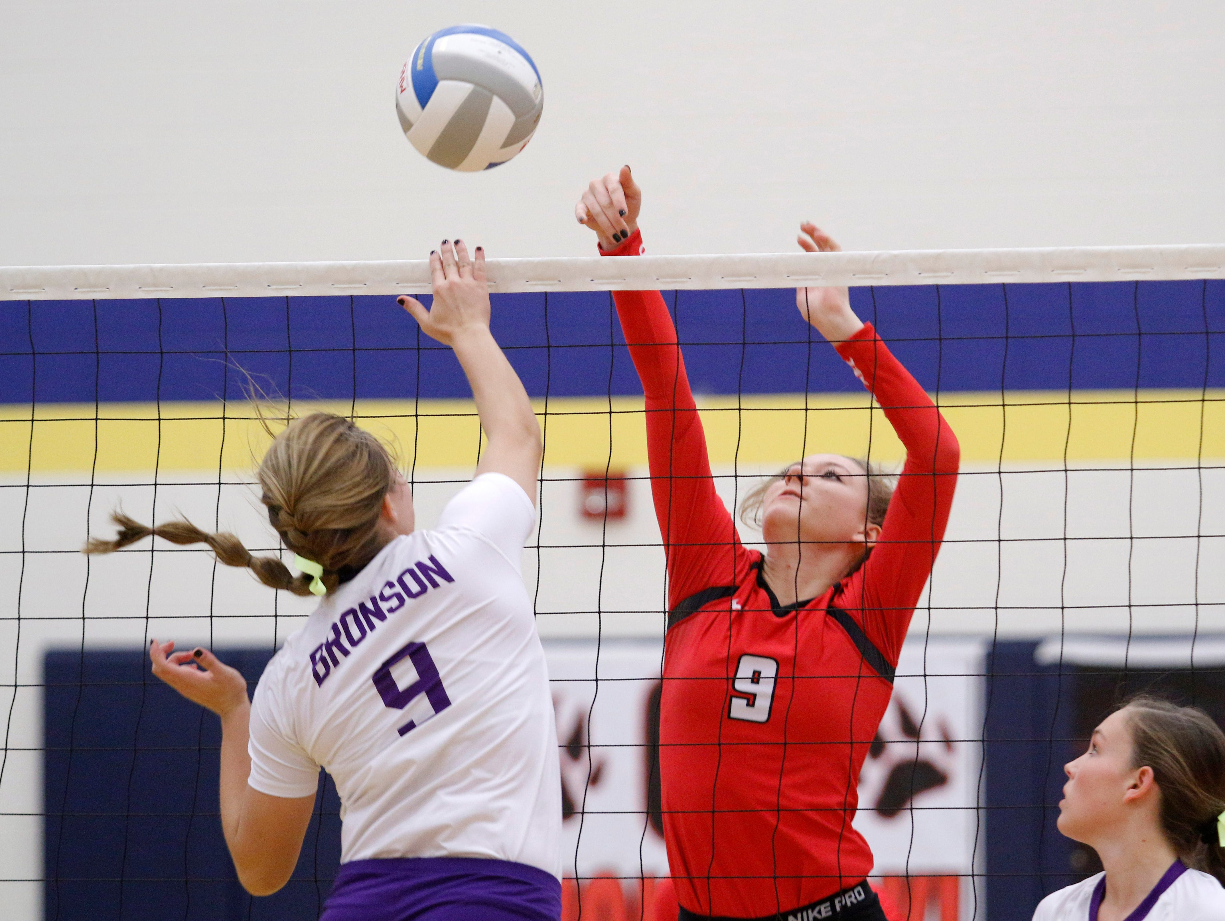 Laingsburg's Maya Ferland, right, and Bronson's Kiana Mayer vie for the ball at the net during their MHSAA quarterfinal game Tuesday, Nov. 15, 2016, in Portage, Mich.