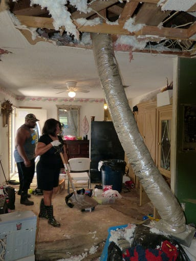 Annie Moultrie and her son, Hosea Moultrie, III, work to try to clean up and salvage whatever was left by recent flood waters that rose over a foot in many areas of her Rolling Hills Road home.  The rain was so heavy it came through their roof destroying the ceiling shown at the top of the photo.