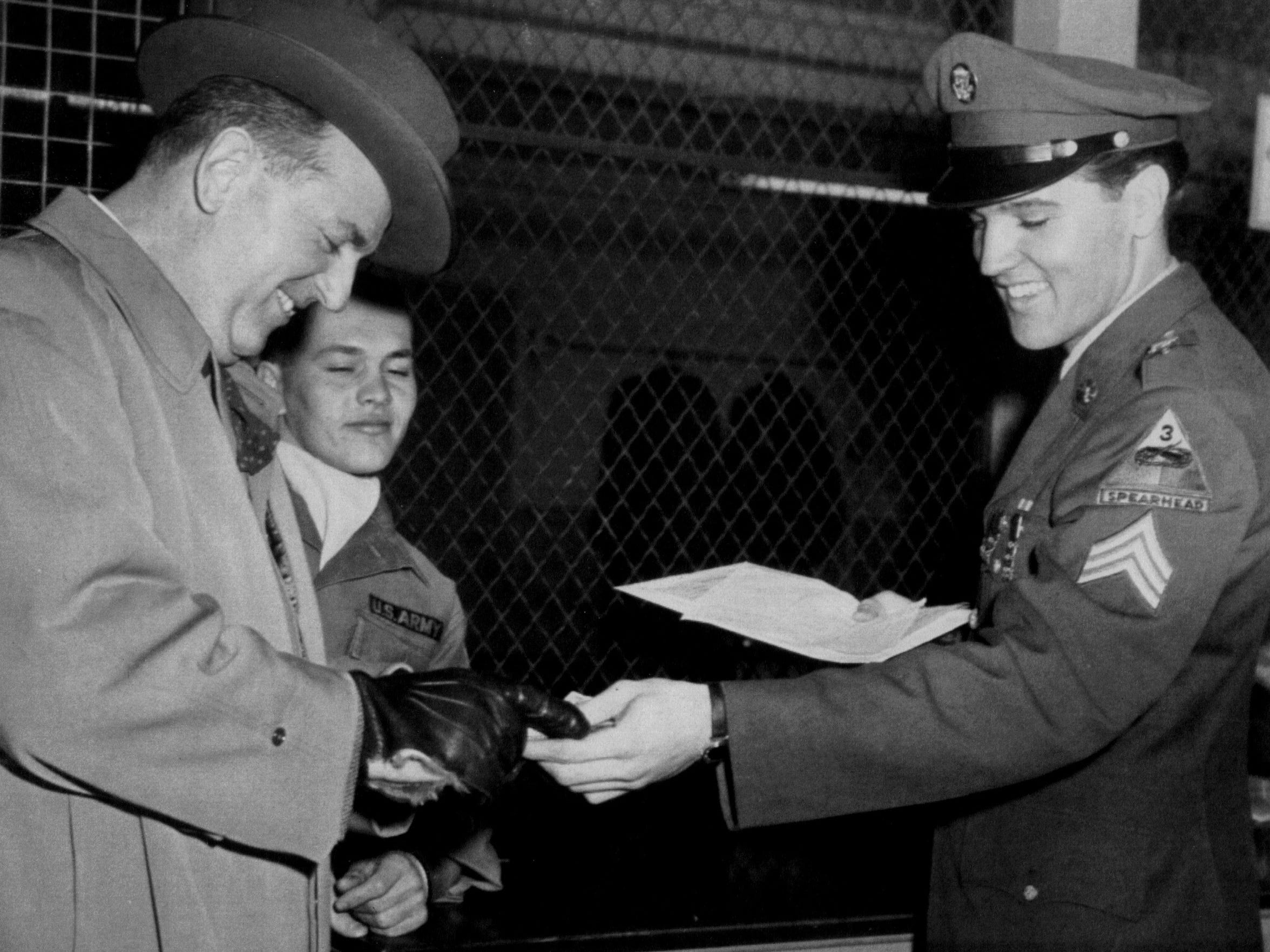 Discharged from the U.S. Army with the rank of sergeant, Elvis Presley grins as he hands his mustering out pay to his business manager, Col. Tom Parker, in this March 5, 1960, photograph. The next day, Elvis would board a train for Memphis, arriving about 7:45 a.m. March 7.