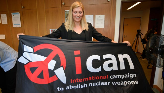 Nuclear disarmament group ICAN executive director Beatrice Fihn holds a banner with their logo after ICAN won the Nobel Peace Prize for its decade-long campaign to rid the world of the atomic bomb as nuclear-fuelled crises swirl over North Korea and Iran, on Oct. 6, 2017 in Geneva.