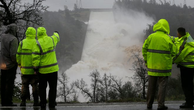 In this Feb. 9, 2017, file photo, water rushes down the damaged Oroville Dam spillway, in Oroville. Over six days, operators of the tallest dam in the United States struggled to figure out their next move after raging floodwaters from California's wettest winter in decades gouged a hole the size of a football field in the dam's main water-release spillway.