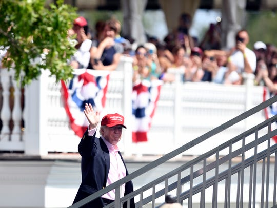 President Donald Trump waves to supporters as he arrives