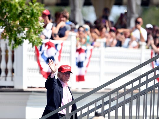 President Donald Trump waves to supporters as he arrives at the course to watch the  final round of the U.S. Women's Open at Trump National Golf Club in Bedminster on Sunday.