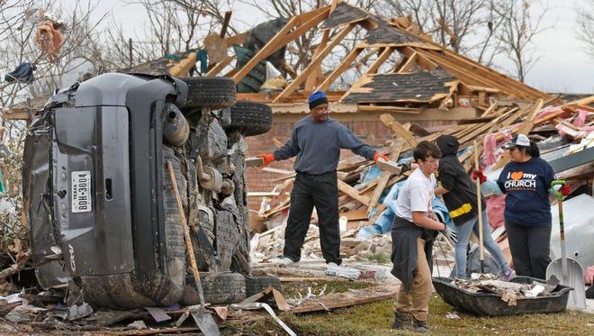 Volunteers help residents clear debris from their tornado-damaged homes in Glenn Heights, Texas, on Jan. 2, 2016.