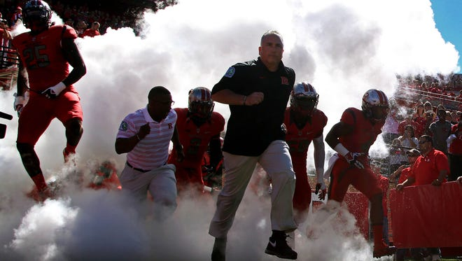 Rutgers Scarlet Knights head coach Kyle Flood leads his team to the field for the game against the Tulane Green Wave at High Points Solutions Stadium.