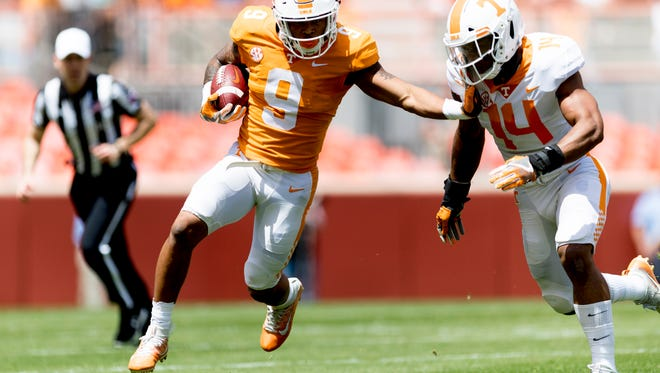 Tennessee running back Tim Jordan (9) runs down the field while pushing away Tennessee linebacker Quart'e Sapp (14) during the Tennessee Volunteers Orange & White spring game at Neyland Stadium in Knoxville, Tennessee on Saturday, April 21, 2018.