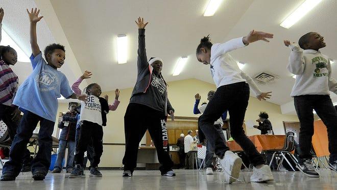 """Nadia Beard (center) leads a dance during """"Art Brightens a Better Generation."""""""