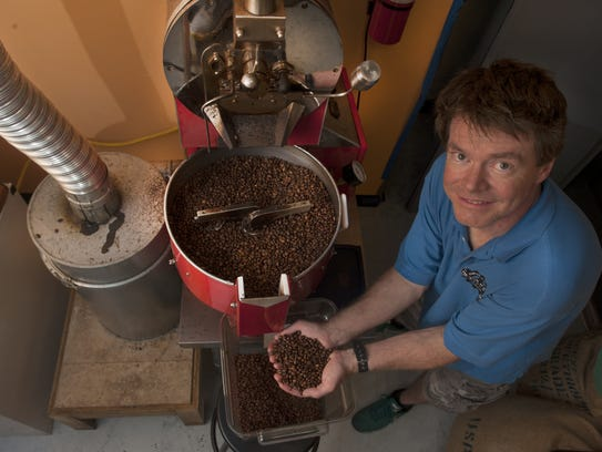 Co-owner Steve McFadden shows some fresh coffee beans from his roasting machine at the Revolution Coffee Roasters in Collingswood. Revolution is collaborating with Flying Fish Brewing Company.