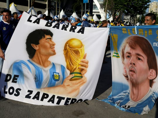 Argentinian fans hold banners with portraits of soccer legend Diego Armando Maradona, left, and Barcelona's soccer star Lionel Messi before the group F World Cup soccer match between Argentina and Bosnia in Rio de Janeiro, Brazil, Sunday, June 15, 2014. (AP Photo/Thanassis Stavrakis)