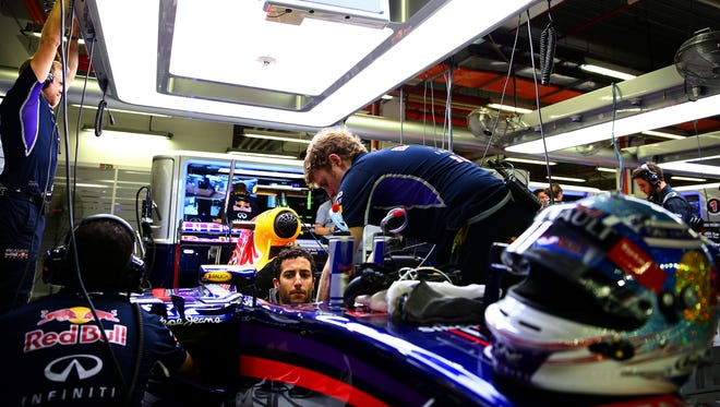 Red Bull's Daniel Ricciardo gets instructions from his team while sitting in his car in the garage during practice for the Singapore Formula One Grand Prix Friday.