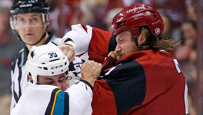 Arizona Coyotes center Ryan White, right, exchange punches with San Jose Sharks center Micheal Haley (38) as they fight during the first period of an NHL hockey game Saturday, Nov. 19, 2016, in Glendale, Ariz.