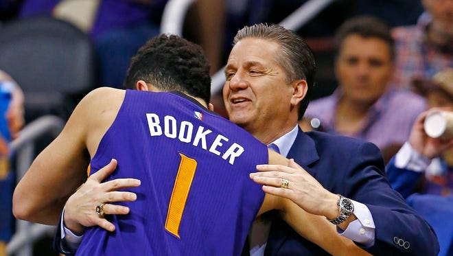 Phoenix Suns' Devin Booker (1) gives Kentucky college basketball coach John Calipari, right, a hug prior to an NBA basketball game against the Los Angeles Clippers, Thursday, March 30, 2017, in Phoenix. Suns' Booker played for Calipari at Kentucky.