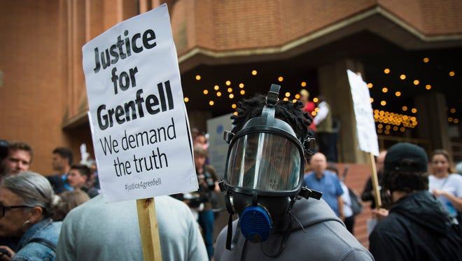 People protest ahead of a meeting of Kensington and Chelsea Council at Kensington Town Hall in west London, on July 19, 2017, the local authority in control of response to the recent Grenfell Tower fire.