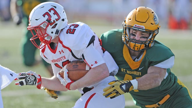 St. Norbert College linebacker Wyatt Veseth (41) tries to tackle Monmouth College running back Trent Rains (23) in the Midwest Conference Championship game on Saturday. Defensive coordinator Ryan Osborn has helped guide the Green Knights to becoming the sixth-ranked scoring defense in NCAA Division III.