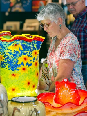 """Jean and Jim Hogue, from Lancaster County Pennsylvania, stop to admire """"Sunflower Basket"""", a piece of blown glass by Dan and Joi LaChaussee Friday evening at the 6th annual Las Cruces Arts Fair held at the Las Cruces Convention Center. LaChaussee Blown Glass display was awarded """"Best of Show"""" by the Dona Ana Arts Council."""