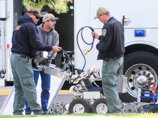 Officers from the Doña Ana Bomb Squad use a robot to