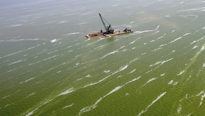 In this Aug. 21, 2013 photo, a dredge barge works along the edge of a large algae bloom in the Toledo shipping channel in Toledo, Ohio.