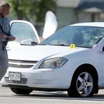 An investigator walks around a car with bullet holes in it as crews investigate an officer-involved shooting May 11 at 31st Street and U.S. 85 in Evans. Weld District Attorney Michael Rourke announced Thursday the officers were justified in shooting the man.