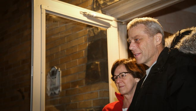Rob Hecksel and his wife MaryRose react after about 100 people flash mobbed their Lansing home, Tuesday, Dec. 19, 2017, to sing Christmas carols for the retired battalion chief and his family.  Hecksel has pancreatic cancer, so about 40 of his Lansing Catholic classmates, along with friends, family, police officers, and fellow firefighters teamed up to bring the family joy in their challenging time.