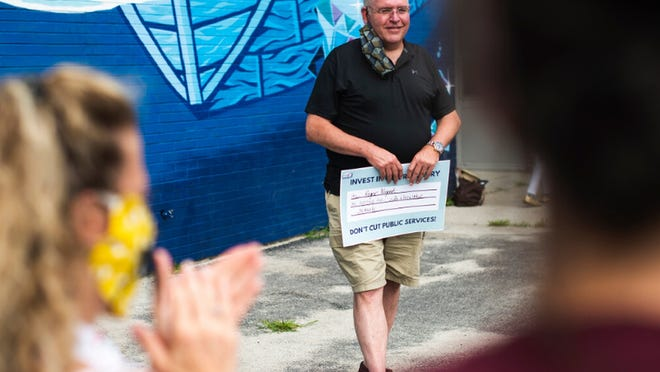 Roger Nugent, president of the Educational Association of Worcester, attends a small rally of the Raise Up Massachusetts coalition at Elm Park Community School on July 22.