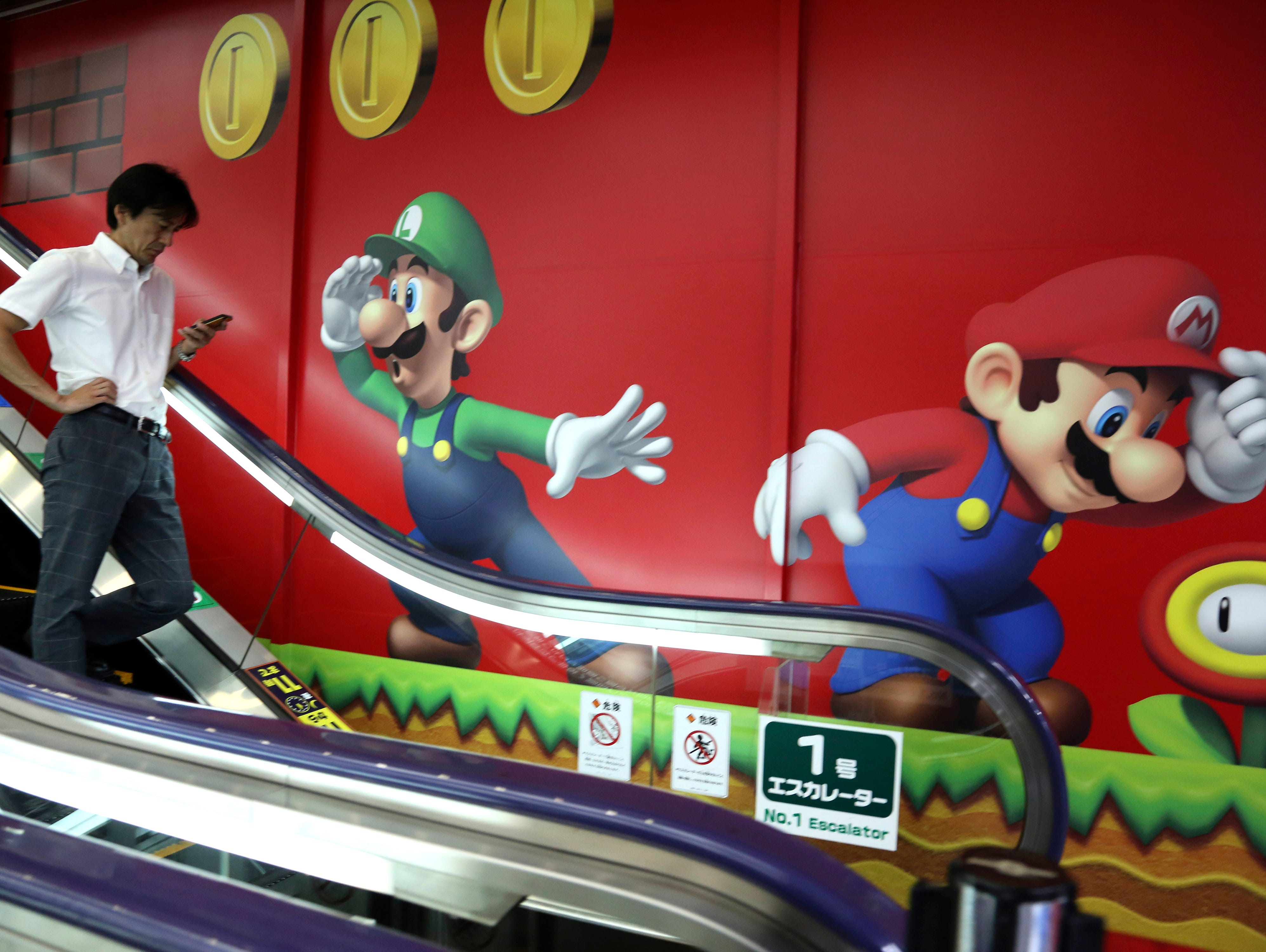 A shopper walks in front of Nintendo's Super Mario characters at an electronics store in Tokyo.