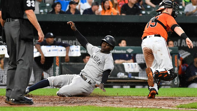 Jun 2, 2018; Baltimore, MD, USA; New York Yankees shortstop Didi Gregorius (18) slides into home plate scoring a run during the sixth inning in front of Baltimore Orioles catcher Chance Sisco (15) at Oriole Park at Camden Yards.