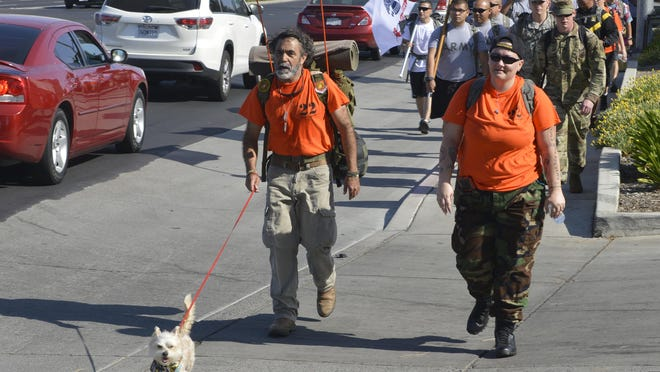 Efraim Ortiz, left, leads the 22 Veterans a Day Suicide Awareness Rucksake Hike along Mooney Boulevard on Friday.