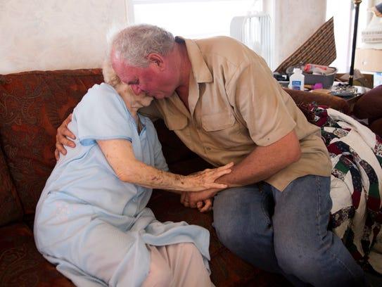 Eddie Rewis Jr. comforts his mother, Lorna Rewis, while