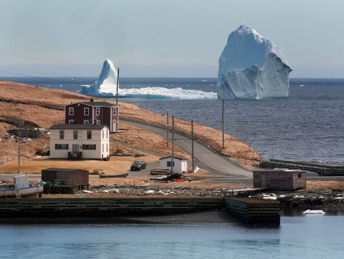 A large iceberg is visible from the shore in Ferryland,