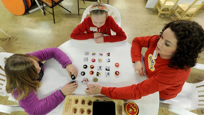Alissa Knoob, 10, left, Baleigh Veach and Shari Veach, right, play the game mancala.