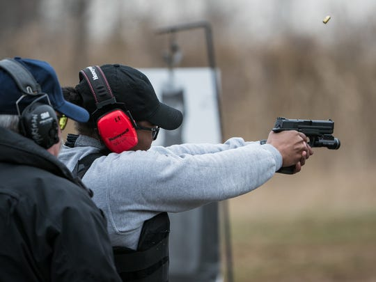 Chrnita Jackson, 25, a former social worker from New Jersey fires her service weapon during a training session in New Castle.