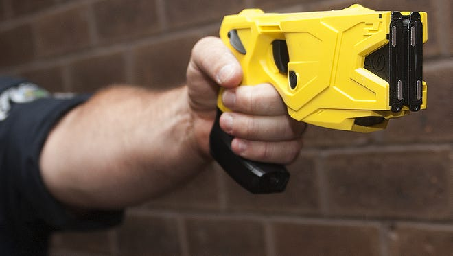 Camden County Police John Martinez points a taser gun that is equipped with a camera on the bottom of the handle in this file photo.