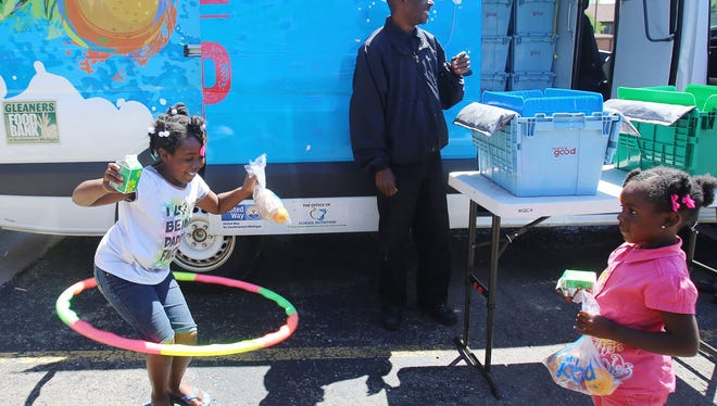 Kalia Nance, 7, left, hula hoops with her lunch in hand that she received from Raynard Liggins at the Sojourner Truth housing development .  Gleaners provides lunch every day to children through a mobile lunch service.  Her sister Rickia Nance, 4, looks on before they head off to play more and have their lunch Wednesday, July 15, 2015.