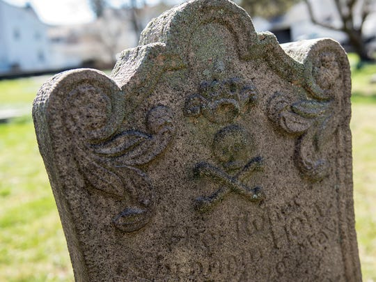 A headstone with a skull and crossbones is one of many different gravestones at the German cemetery in Hanover Borough.