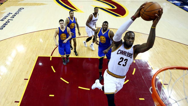 Cleveland Cavaliers forward LeBron James (23) dunks the ball against Golden State Warriors center Festus Ezeli (31)  in game six of the NBA Finals at Quicken Loans Arena.