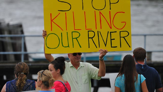 John Kane, of Palm City, protests in front of the St. Lucie Locks, where water from Lake Okeechobee is released into the St. Lucie River Estuary, during an Indian River Lagoon Rally at Phipps Park and the St. Lucie Locks in Tropical farms in this 2013 file photo. An estimated 5,000 participated in the event.