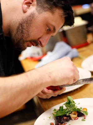 Chef Joe Tripp finishes off a plate for customers Tuesday, Feb. 23, 2016, in the kitchen at Alba in Des Moines. Tripp was nominated for a James Beard Foundation Award for his work at the East Village restaurant. He is working on a small plates spot on Ingersoll Avenue to open in March 2017.