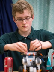 Seton Catholic Central eighth-grader Caleb Woodley-Dickinson works on a his robot during a meeting of the robotics club on Jan. 17.