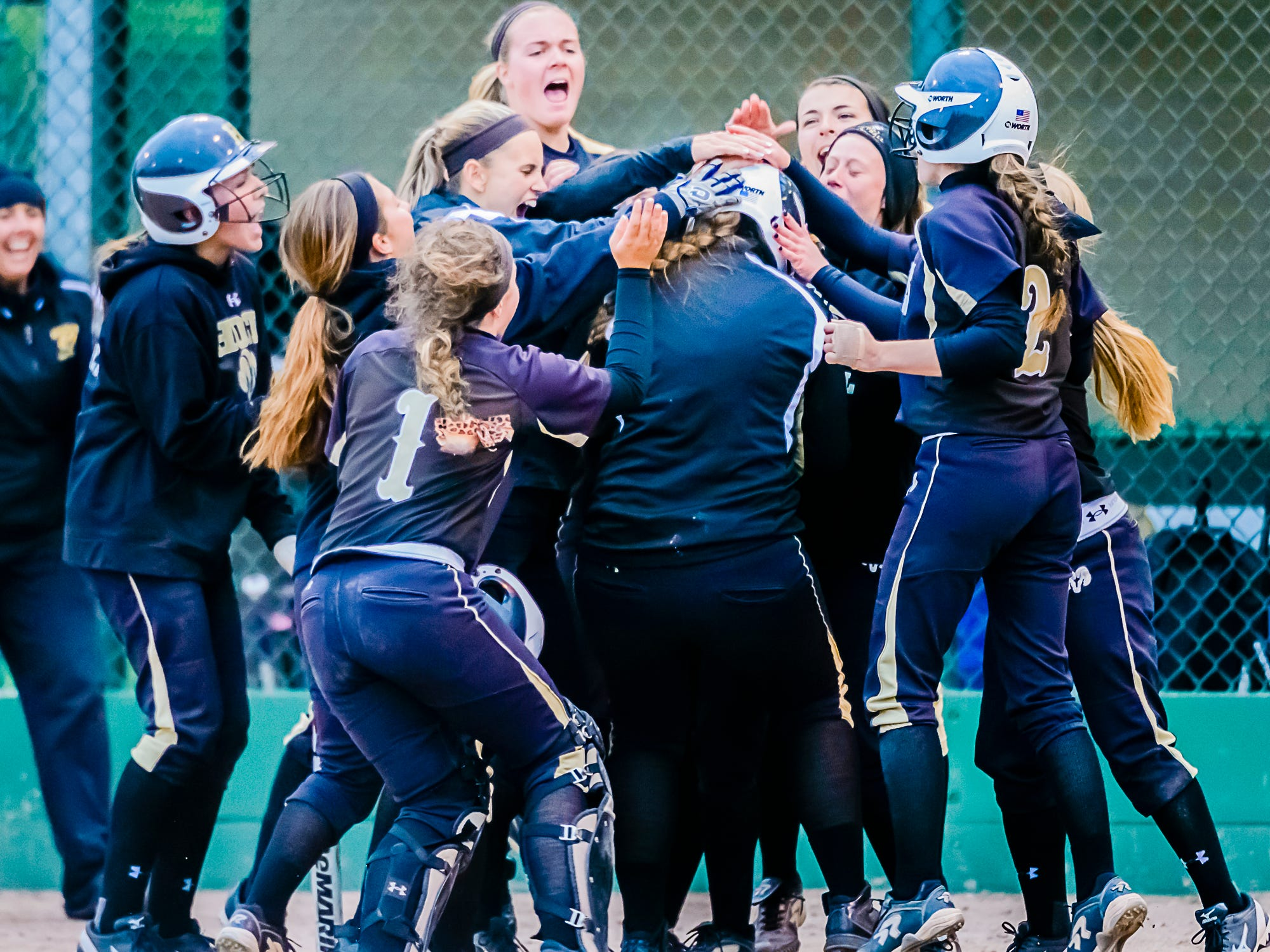 Mackinley Lane ,center, of Holt is congratulated by her teammates after hitting a 2-run homer in the 3rd inning of their Softball Classic championship game with St. Johns Tuesday May 19, 2015 at Ranney Park in Lansing. KEVIN W. FOWLER PHOTO