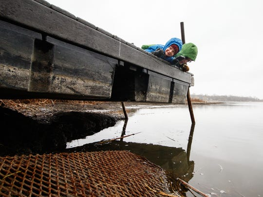 Two-year-old Eric Langford and his father Luke watch minnows from the pier at School Section Lake in Ottawa on Saturday, April 14, 2018. A broken dam on the lake has caused extremely low water levels.
