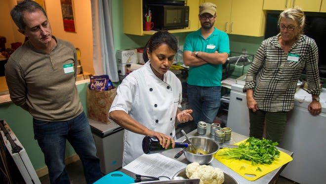 Chef Jes Thomas, center, demonstrates during a Taste of India cooking demonstration at the Central Collective in Knoxville on Sunday, Dec. 11, 2016.