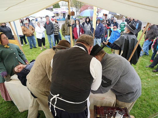 Visitors watch a typical medical procedure on the battleground Saturday at the Civil War Show at the Richland County Fairgrounds.